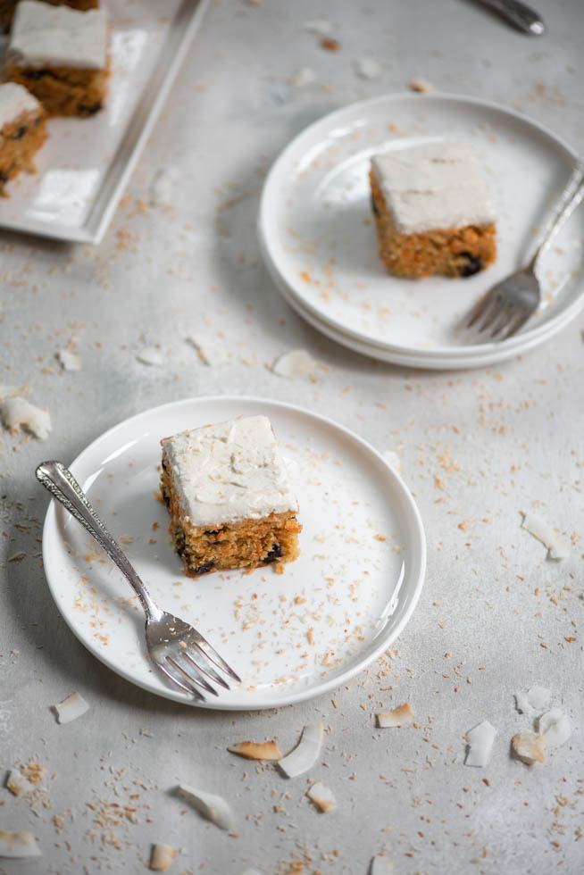 45 view of frosted carrot cake on white plate