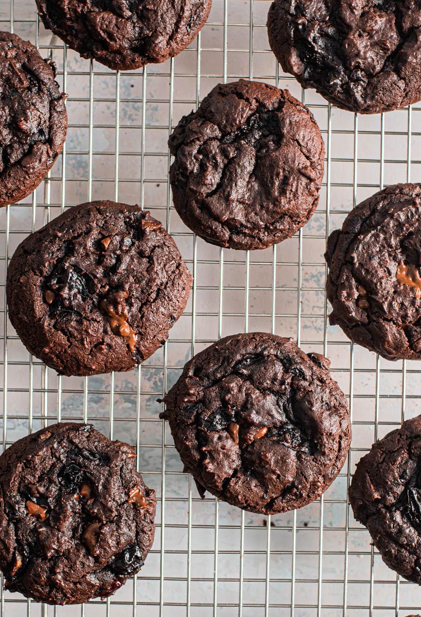 closeup of dark chocolate cherry brookies (brownie cookies) on cooling rack